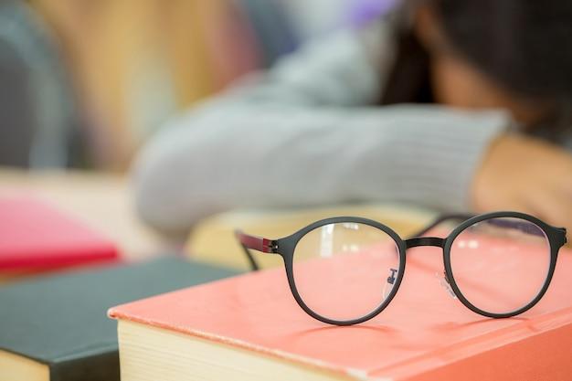 Feche acima dos vidros do olho na mesa de madeira e no livro de texto na biblioteca. Foto gratuita