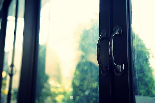 Feche acima em uma entrada do restaurante. portas de vidro duplo, maçanetas de porta de aço preto Foto Premium