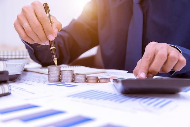 Feche acima, mão que põe a pilha das moedas do dinheiro no dinheiro da economia e no conceito crescente do negócio. Foto Premium