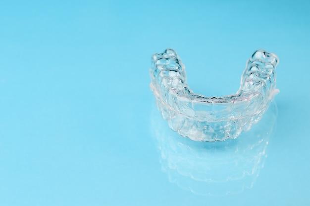 Feche alinhadores invisíveis no fundo azul com espaço de cópia. aparelhos plásticos, retentores odontológicos para endireitar os dentes. Foto Premium
