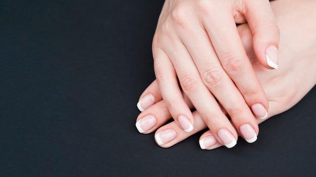 Feche as mãos da mulher em fundo preto Foto Premium