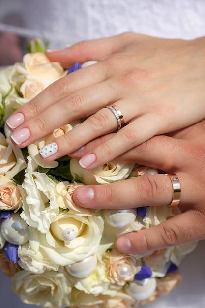 Feche as mãos da noiva e do noivo com buquê de casamento e anéis de ouro Foto Premium