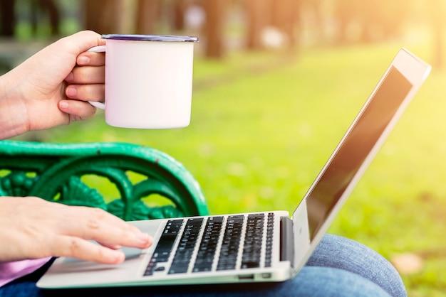 Feche as mãos de uma mulher segurando uma xícara de café. garota usando um laptop de manhã. Foto Premium