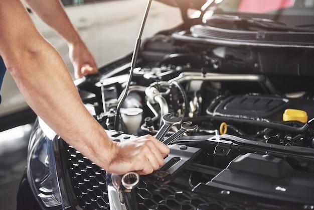 Feche as mãos do mecânico irreconhecível, fazendo serviço e manutenção do carro. Foto gratuita