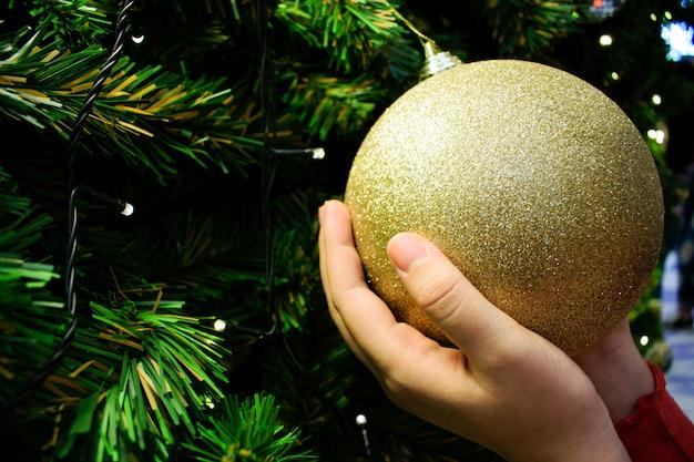 Feche as mãos femininas segurando uma bola de ouro. árvore de natal decorada em prata Foto Premium