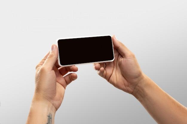 Feche as mãos masculinas segurando o telefone com tela em branco durante a visualização on-line de partidas e campeonatos de esporte popular em todo o mundo. Foto gratuita