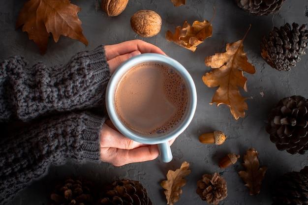 Feche as mãos segurando uma xícara de chocolate hoc Foto gratuita