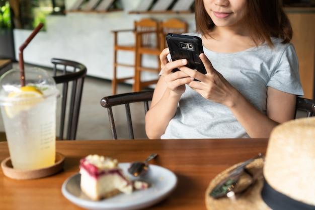 Feche das mãos das mulheres segurando o telefone móvel no café. Foto Premium