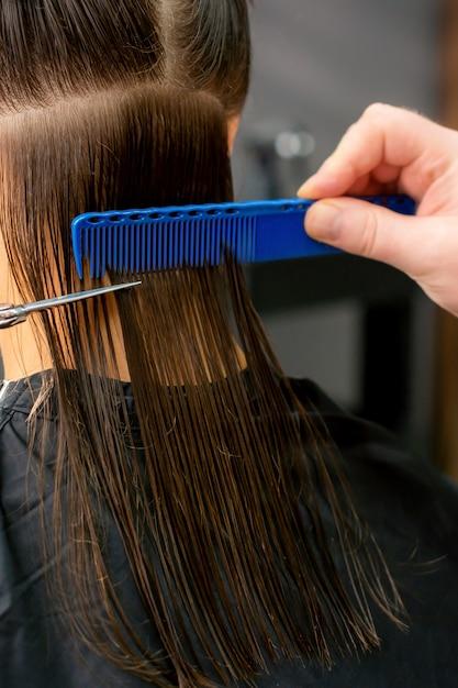 Feche das mãos do cabeleireiro masculino, cortando os cabelos longos de uma jovem segurando uma tesoura e um pente no salão. visão traseira Foto Premium