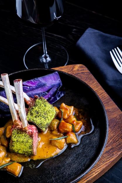 Feche de costeletas de cordeiro com legumes com um molho de caramelo, pimenta e especiarias em um ambiente de restaurante. Foto Premium