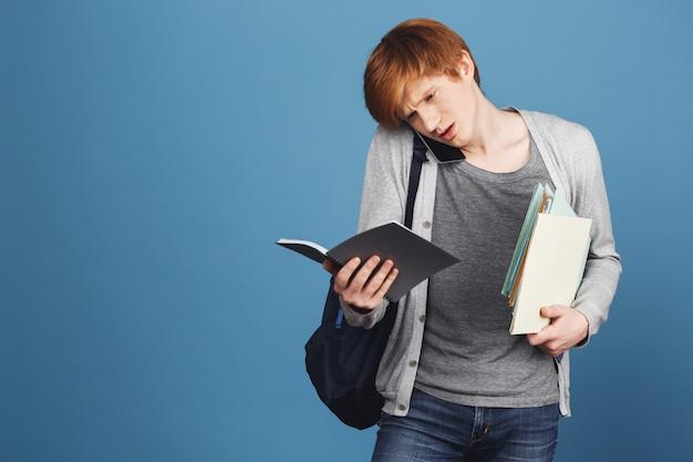 Feche de estudante do sexo masculino gengibre bonito jovem em roupas casuais cinza com mochila segurando livros nas mãos, falando no telefone com o amigo, tentando entender a caligrafia no caderno. Foto gratuita
