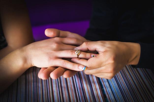 Feche de jovem, colocando no anel de noivado de dedo de namorada durante um jantar romântico. Foto Premium