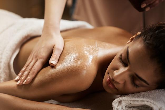 Feche de linda mulher africana, desfrutando de massagem no salão spa. Foto gratuita