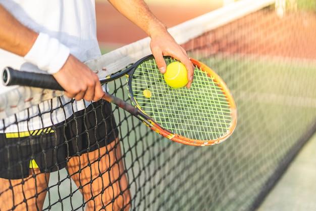 Feche de mãos de jogador de tênis segurando raquete com bola. Foto Premium