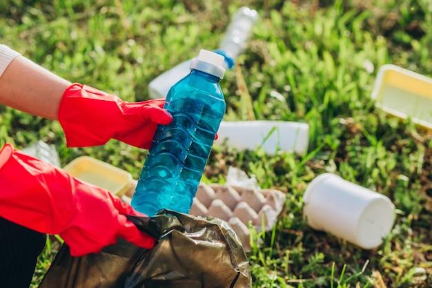 Feche de mãos femininas usando luvas vermelhas e usando o saco de lixo, pegando lixo plástico para limpeza no parque. Foto Premium