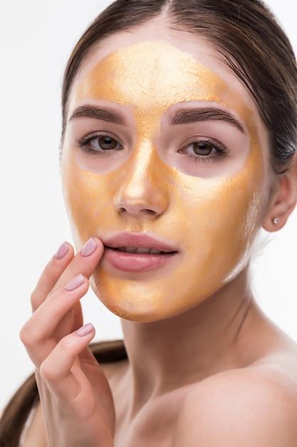Feche de mulher jovem e saudável com ouro máscara cosmética na pele macia. Foto gratuita