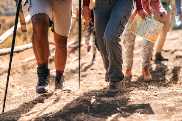 Feche de pernas dos caminhantes subindo na montanha. tempo de outono. Foto Premium