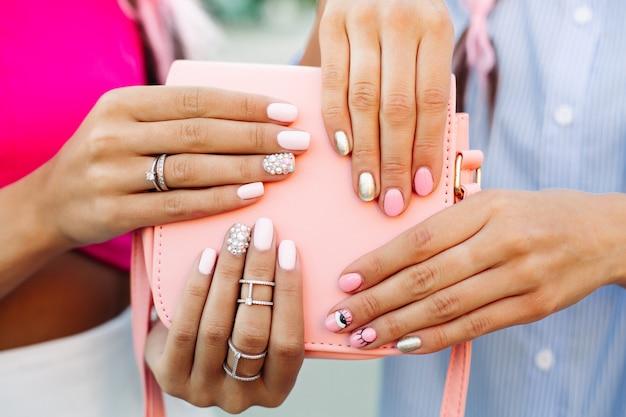 Feche de saco com mãos de meninas com manicure por cima. Foto Premium