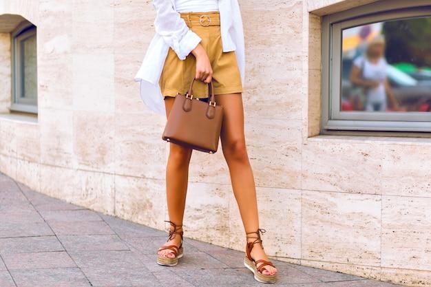 Feche detalhes de moda de corpo inteiro de pernas esguias de mulher bronzeada, andando na rua vestindo shorts bege de linho, bolsa de couro caramelo de luxo, camisa branca e sandálias da moda gladiador. Foto gratuita