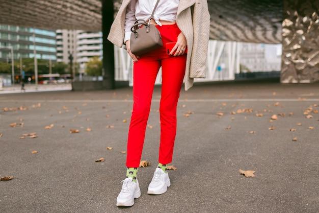 Feche detalhes de moda, jovem vestindo calças vermelhas da moda, meias engraçadas e tênis de moda feio, casaco bege elegante, posando na rua perto de centros de negócios, tempo de outono. Foto gratuita