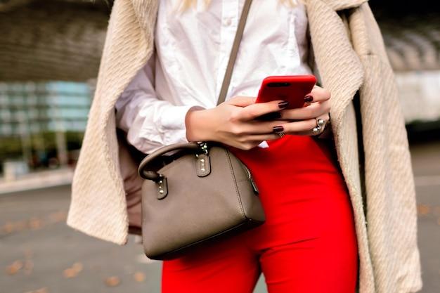 Feche detalhes de moda, mulher de negócios, bateu em algo em seu telefone, fundo urbano da cidade de outono, terno brilhante e casaco de caxemira, pronto para a conferência. Foto gratuita