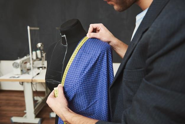 Feche detalhes do talentoso profissional jovem caucasiano masculino designer trabalhando no vestido novo para a coleção de primavera, verificando tamanhos com fita métrica, passando o dia em sua oficina Foto gratuita
