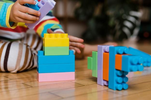 Feche garotinho brincando com brinquedos Foto gratuita