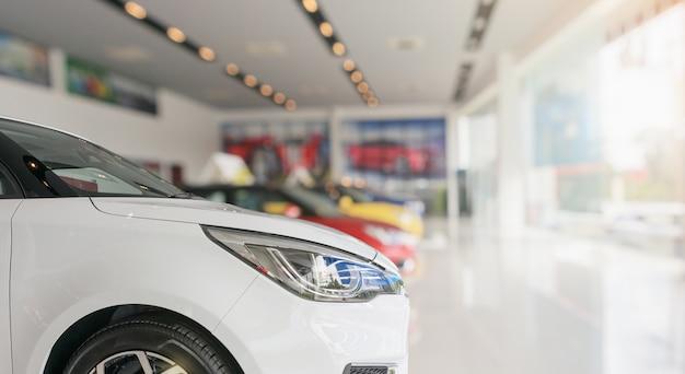 Feche na frente do carro novo no fundo do showroom Foto Premium