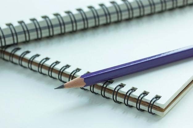 Feche o caderno espiral e lápis, ponto de foco seletivo Foto gratuita