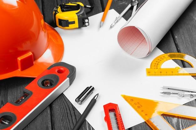 Feche o capacete de segurança laranja e variedade de ferramentas de reparo Foto Premium