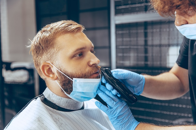 Feche o homem cortando o cabelo na barbearia usando máscara durante a pandemia de coronavírus. Foto gratuita