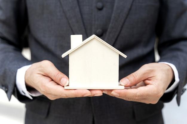 Feche o homem de negócios asiáticos segurando a casa modelo - conceito de finanças empresariais. Foto gratuita