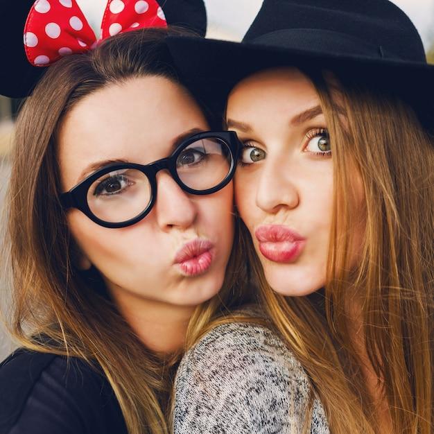 Feche o retrato bonito de estilo de vida de duas melhores amigas fazendo auto-retrato, se divertindo, sorrindo. aproveitando o tempo juntos, clima de primavera. maquiagem natural. meninas loiras e morenas. chapéu estiloso. Foto gratuita