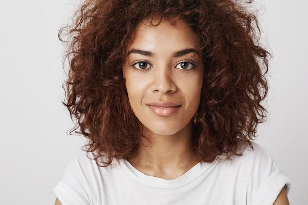 Feche o retrato da bela garota africana com olhos grandes, sorrindo com um sorriso, sentindo-se confiante e calmo, sendo atraente e atraente. Foto gratuita