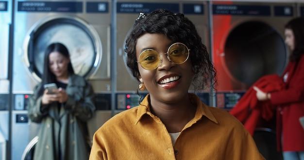 Feche o retrato da bela jovem afro-americana em óculos de sol amarelos, sorrindo alegremente para a câmera na lavanderia pública com máquinas de lavar Foto Premium