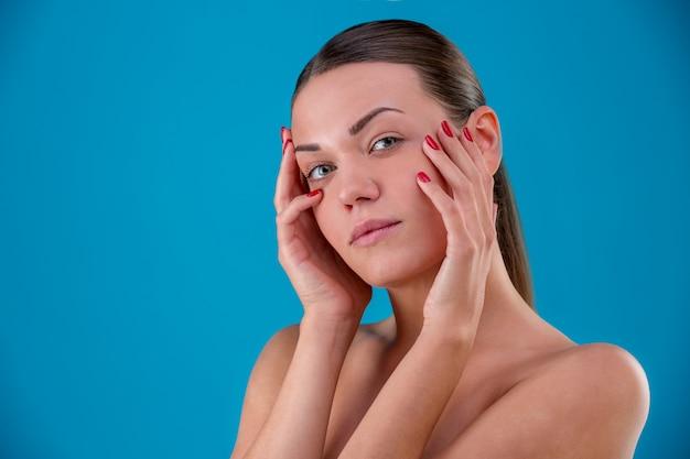 Feche o retrato da beleza da morena jovem sorrindo e tocando seu rosto em azul. pele fresca perfeita. cuidados com a pele e juventude. Foto Premium