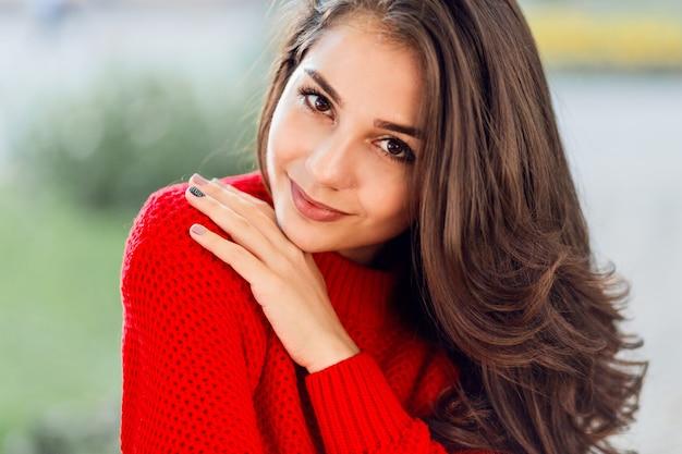 Feche o retrato da beleza da mulher morena com cabelos compridos ondulados, sorriso fofo relaxante no parque outono. Foto gratuita