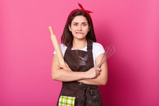 Feche o retrato da dona de casa pensativa com avental marrom, faixa de cabelo vermelho, camiseta branca. fêmea bonita fica com as mãos cruzadas, morde o lábio e não consegue se lembrar dos ingredientes certos para fazer torta. Foto Premium