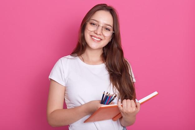 Feche o retrato da menina bela estudante pronta para fazer anotações no caderno, tendo uma aparência agradável Foto gratuita
