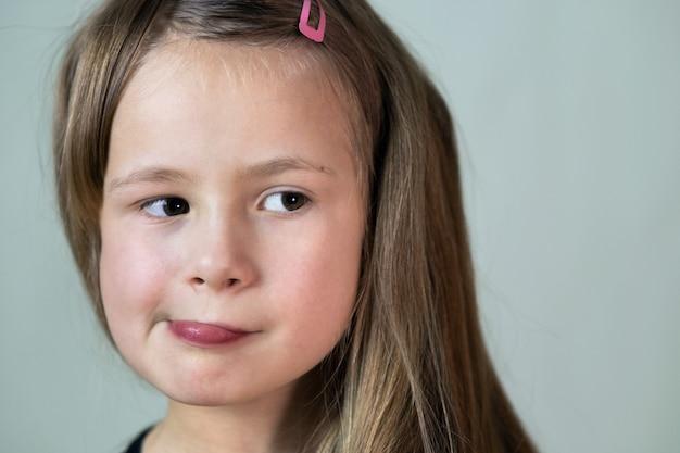 Feche o retrato da menina criança com expressão de rosto engraçado. Foto Premium