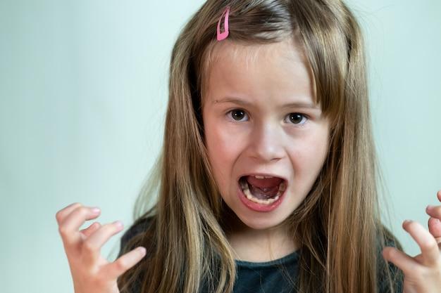 Feche o retrato da menina criança gritando com raiva, olhando agressivamente Foto Premium