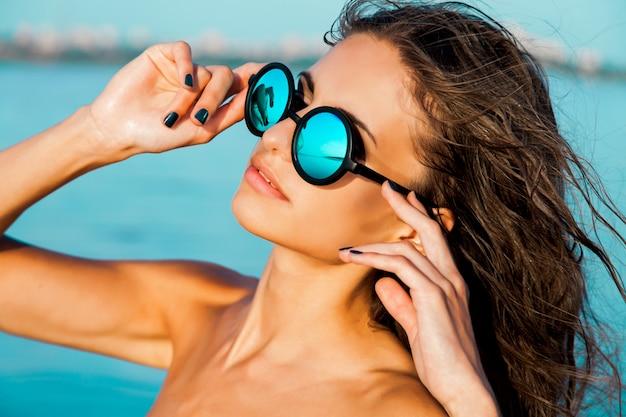 Feche o retrato da menina sexy bonita elegante de óculos e cabelos molhados em uma praia ensolarada com água azul. tome banhos de sol e aproveite o resto. Foto gratuita