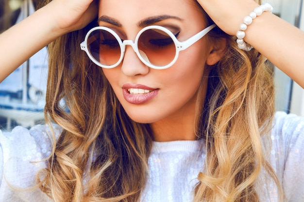 Feche o retrato da moda de uma mulher bonita com uma pele perfeita e um grande sorriso incrível, tenha cabelos cacheados fofos loiros, vestindo uma camisola branca com brilhos, pulseira de pérolas e óculos de sol redondos. Foto gratuita