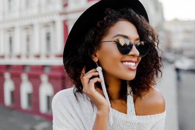 Feche o retrato da moda mulher negra com cabelos afro elegantes posando ao ar livre. meio urbano. usando óculos escuros pretos, chapéu e brincos brancos. acessórios da moda. sorriso perfeito. Foto gratuita