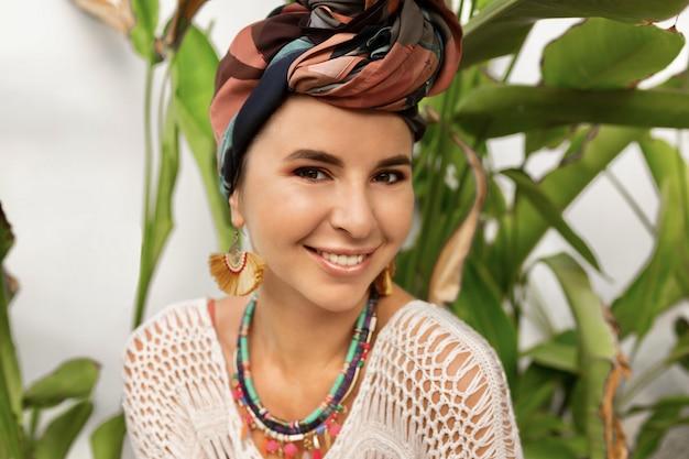 Feche o retrato da mulher rindo com um turbante na cabeça posando sobre palmeiras Foto gratuita