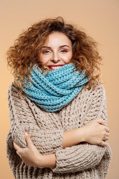 Feche o retrato de alegre sorridente menina morena linda encaracolada na camisola de malha e pescoço cinza sobre parede bege Foto gratuita