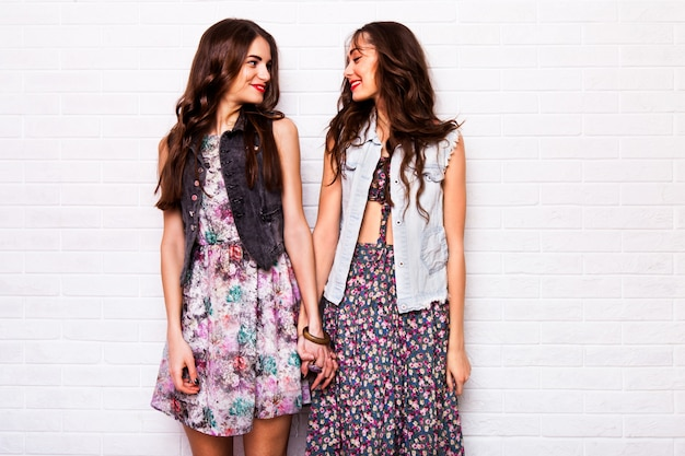 Feche o retrato de duas melhores amigas hipster bonita usando vestido colorido boho, jaqueta elegante e enfeites. as meninas sorriem, divirtam-se contra a parede branca urbana. Foto gratuita