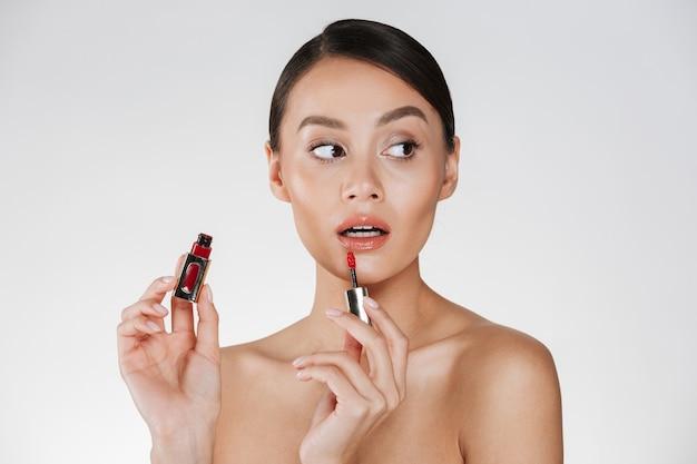 Feche o retrato de estúdio de uma mulher morena com pele macia, aplicar gloss vermelho nos lábios e desviar o olhar, isolado sobre o branco Foto gratuita