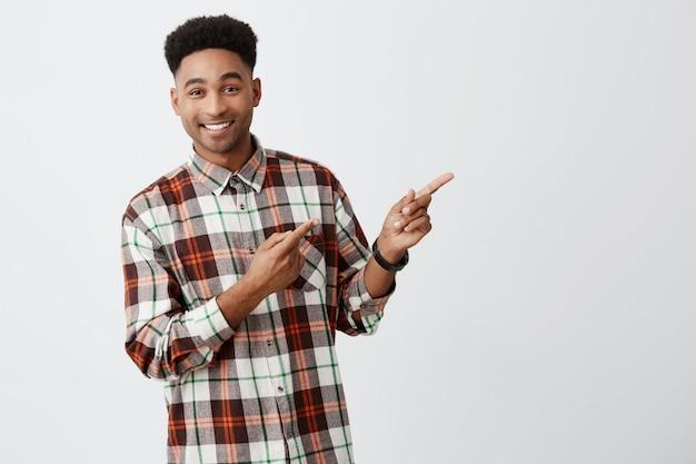 Feche o retrato de jovem homem de pele escura bonito com cabelo afro escuro elegante camisa quadriculada, sorrindo com dentes, apontando para o lado ganhou parede branca com expressão feliz e alegre Foto gratuita