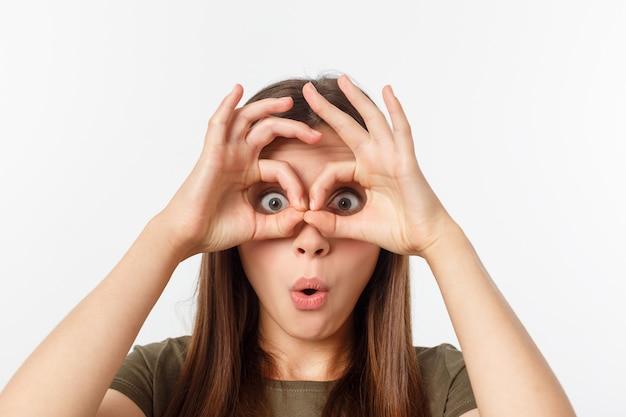 Feche o retrato de menina alegre, fofa, elegante, atraente, na moda, fazendo binóculos com os dedos, isolados no fundo cinza, de bom humor Foto Premium